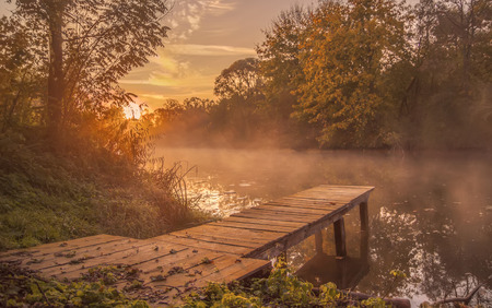 Landscape.bridge frost wooden on the shore in the morning mist.late fall