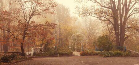 Landscape. romantic gazebo in the park in the morning fog. late fall