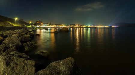 panorama, horizontal view of Crimean mountains with rocky coastline of Black sea with city lights on the background.Night luminous embankment