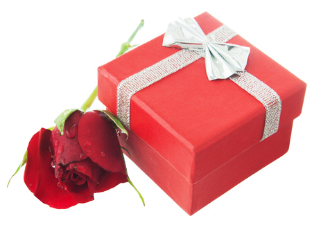 Red greeting box with silver ribbon,bow and little red rose near. Isolated white background