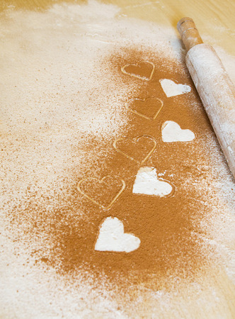 throe: Valentine background, greeting card. Meal white hearts, wheat meal and cacao, cinnamon on the desk. Your text on the card. Stock Photo