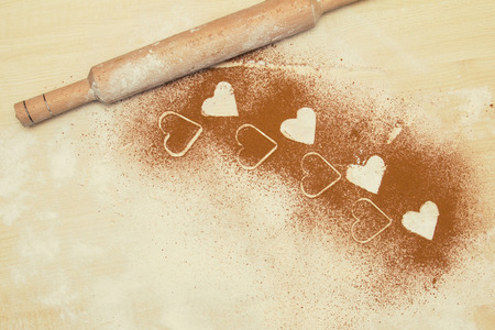 throe: Valentine background,greeting card.Frame of hearts.Meal white hearts, wheat meal and cacao, cinnamon on the desk.Your text on the card