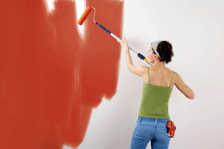 Woman painting on wall using paint roller