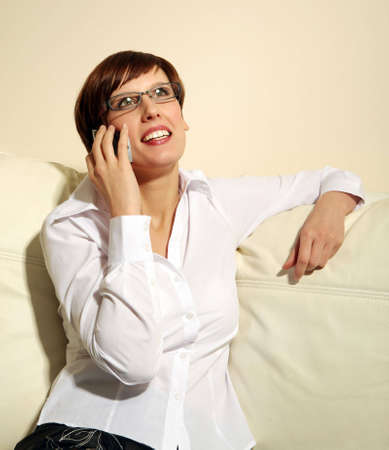 mobilephones: Woman on sofa using mobile phone, close-up