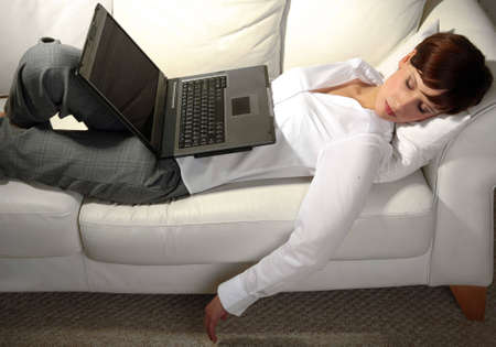 beautiful bangs: Young business woman sleeping on sofa, laptop resting on stomach