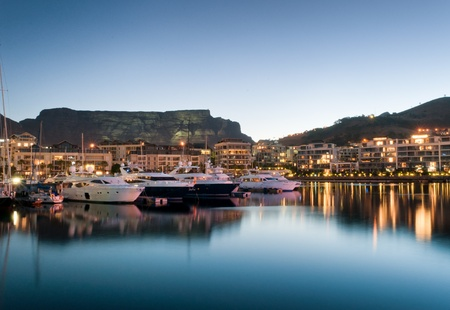 cape town: Victoria and Alfred Waterfront as the hot summers sun sets behind Table Mountain and the night lights start to shine Stock Photo