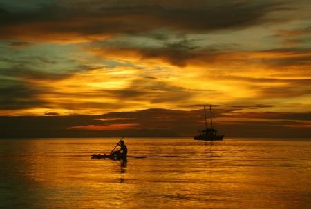 航行ボートの海、美しい黄金の夕日の男上 写真素材