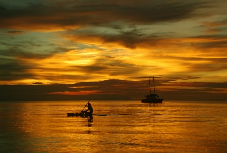 rowing: Sailing boat on the sea, a man on a beautiful golden sunset Stock Photo