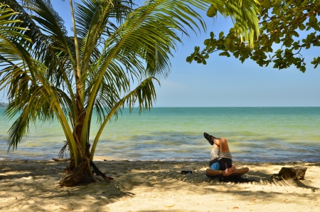 under tree: Man resting under a palm tree by the sea Stock Photo