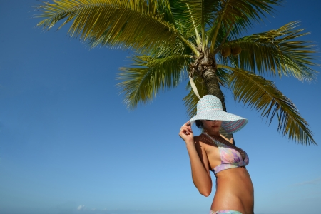 sensuous: Woman in summer hat sunbathing under a palm tree on a background of blue sky  Island Roatan