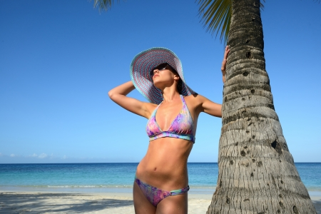 Woman in summer hat sunbathing under a palm tree on a background of blue sky  Island Roatan photo