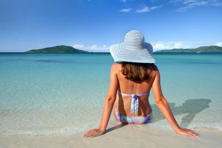 Dívka v letní klobouk ležící na písku a podívat se na oblohu na pozadí krásných ostrovů
