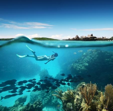 Jonge vrouw snorkelen in de koraalriffen in de tropische Caribische zee