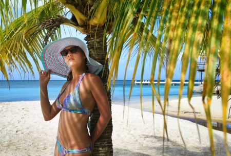 Beautiful woman in a hat standing under palm branches on the background of the Caribbean  Honduras  photo