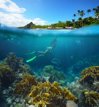 Viaja tarjeta con una mujer flotando en una isla tropical y los arrecifes de coral en primer plano.