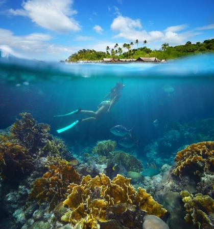 Travel karta s ženou plovoucí na pozadí zelených ostrůvků a korálovým útesem v popředí. Reklamní fotografie