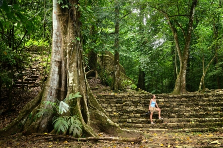 A woman inspects less studied archaeological structures in the jungle in the ancient Mayan city of Palenque, Mexico