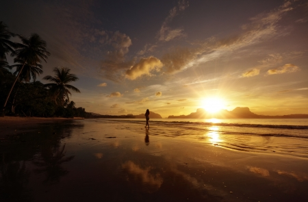 Woman walking on the beach against the setting sun over the island
