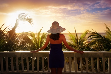 A woman on a balcony looking at the beautiful Caribbean sunset. Stock Photo - 19148220