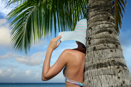 Woman under a palm tree watching the ocean dream. photo