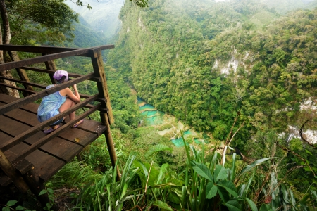 Photographer on the lookout point on the Cascades National Park in Guatemala Semuc Champey