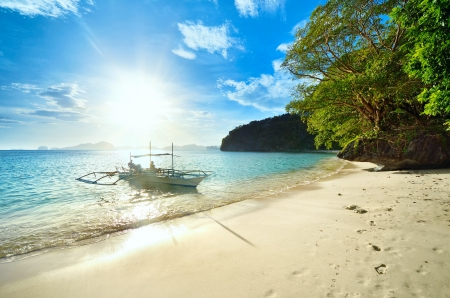 Travelers meet the sunset on a wild beach against the islands of El Nido  Philippines  photo