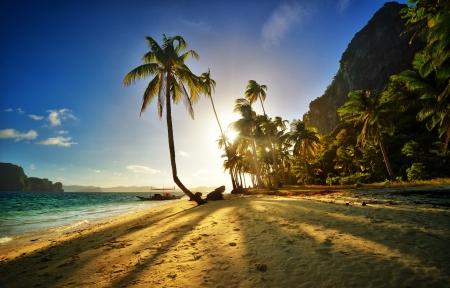 Krásná písečná pláž při západu slunce na ostrově v El Nido Filipínách