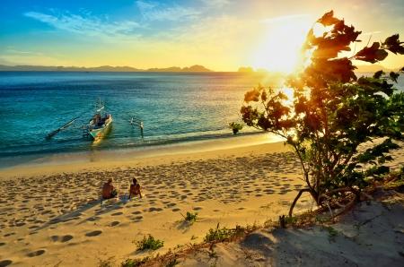 Mladý šťastný pár se těší krásný západ slunce na pláži ostrova El Nido