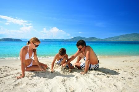 viaje familia: Familia feliz que se relaja en la playa en un fondo de las islas Foto de archivo