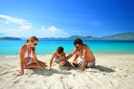 family vacation: Happy family relaxing on the beach on a background of the islands  Stock Photo