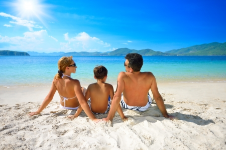 Happy family sunning on the beach on the background of the islands  Stock Photo