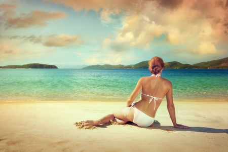Beautiful woman in white bikini sunbathing on the beach on the background of the islands  photo