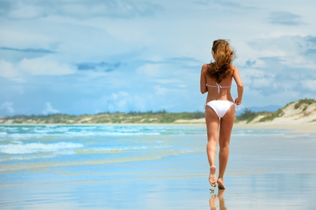 A woman running along the beach in a white bikini  photo