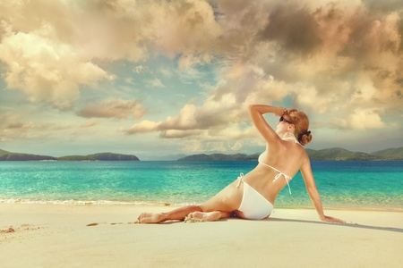 Beautiful woman relaxing on a sunny white sandy beach on the background of the islands photo
