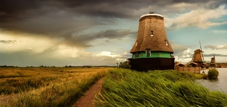 watermanagement: Against the background of storm clouds around the lake are old Windmills
