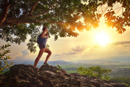 Young woman admires the sunset with a backpack standing on cliff edge