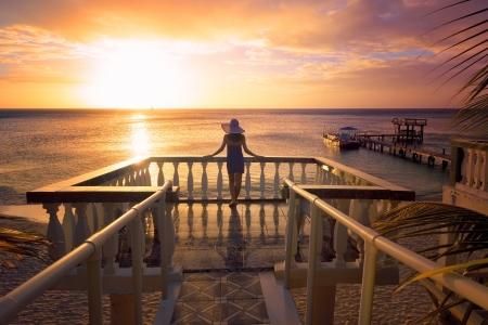 Una mujer con un sombrero mirando a la romántica puesta de sol del Caribe mientras está de pie en el balcón Isla Roatan, Honduras Foto de archivo - 21494770
