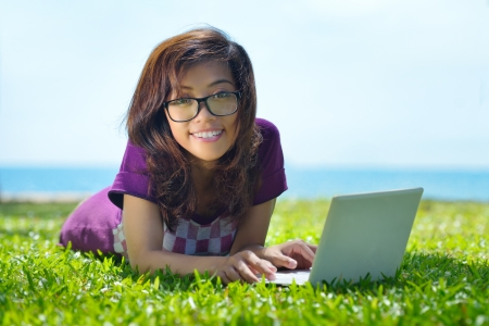 Young smiling student is involved with laptop on the green grass Banco de Imagens - 21494773