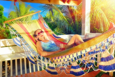 Beautiful woman relaxes on a hammock in a tropical garden. photo
