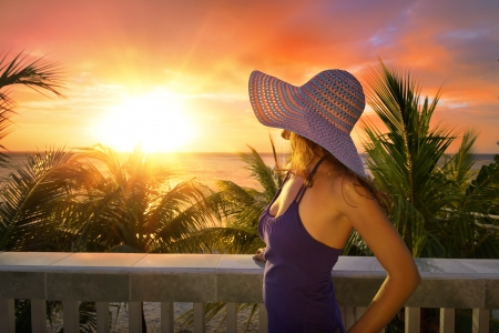 A woman on a balcony looking at the beautiful Caribbean sunset.