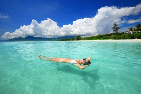 Woman in bikini relaxing lying on the water against the background of the beach and the mountains