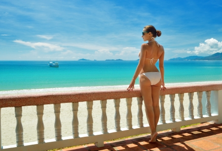 Beautiful woman in bikini on the terrace admiring the sea.
