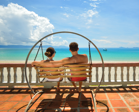 Resting happy couple swinging on a swing looking at the blue sea  Vietnam  photo