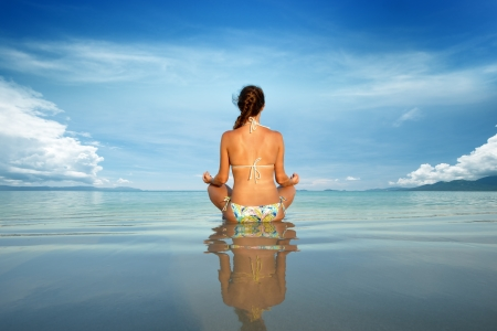 bound: Young beautiful woman in a lotus position on a background of blue sky and island  Stock Photo