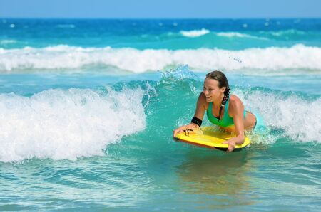 Young attractive woman bodyboards on surfboard with nice smile  Banco de Imagens