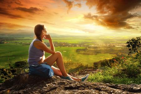 Žena sedí na okraji útesu a díval se na slunné údolí a hory