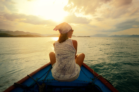 boat: Woman traveling by boat at sunset among the islands  Stock Photo