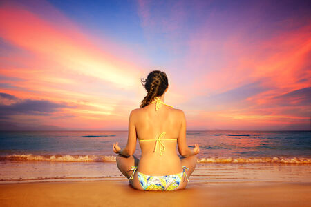 Woman in lotus position on a background of sunset  photo