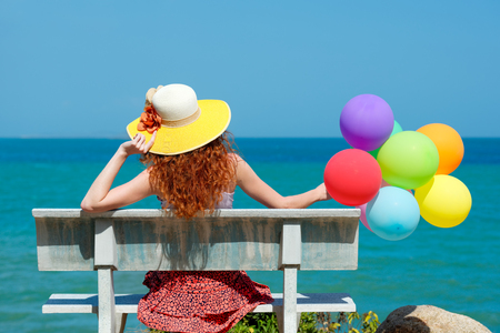 Happy woman in a hat with balloons Banco de Imagens