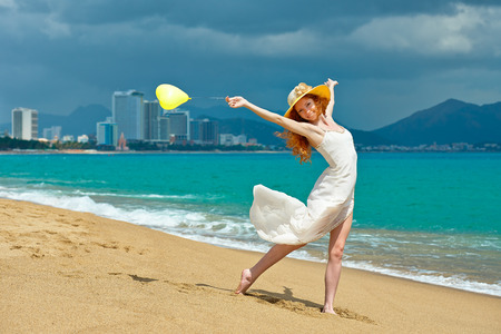 Young happy woman running with balloon on the beach at the resort town of Nha Trang Vietnam photo